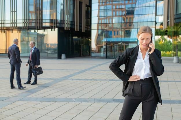Grave giovane imprenditrice in tuta ufficio parlando al cellulare all'aperto. imprenditori e città edificio facciata in vetro in background. copia spazio. concetto di comunicazione aziendale