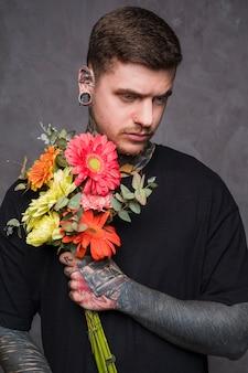 Grave giovane uomo con il naso trafitto e le orecchie tenendo in mano il bouquet di fiori