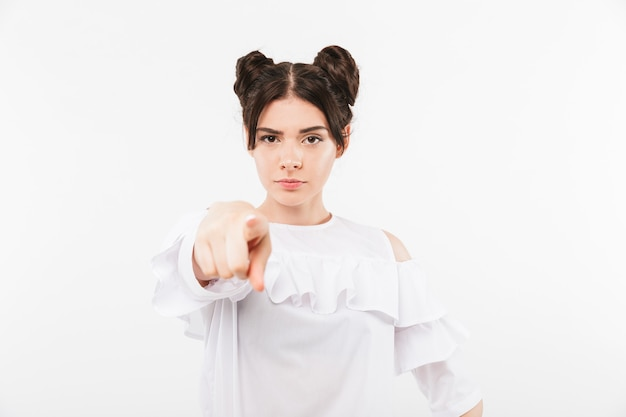 Grave ragazza rigorosa con doppia acconciatura panini dito puntato con colpa, isolato su bianco