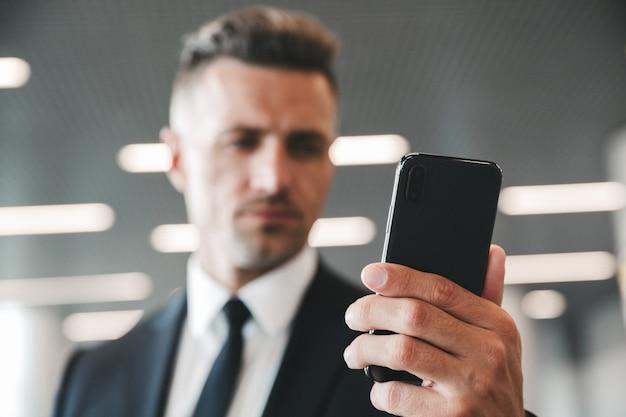 Grave uomo d'affari maturo guardando il telefono cellulare