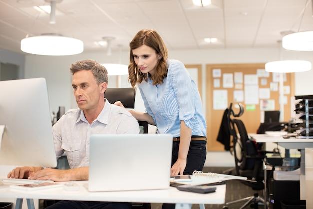 Gravi colleghi di lavoro che lavorano insieme su computer desktop