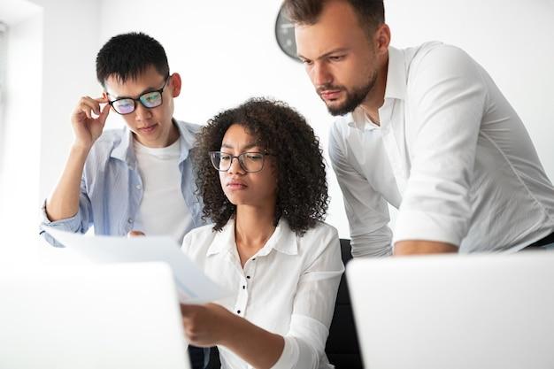 Gravi ingegneri di software multirazziale che leggono i dati dal documento e pensano mentre lavorano insieme in ufficio