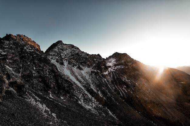 Gray rock mountain with white snow durante il graphy di sun rise aerial