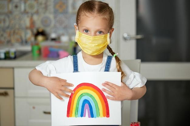 Grazie a nhs. ragazzo in maschera protettiva che dipinge l'arcobaleno durante la quarantena covid-19 a casa. focolaio di coronavirus covid-19.