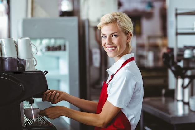 Grazioso barista che usa la macchina del caffè