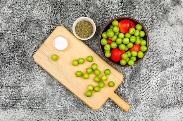 Greengages e pesche con una piccola barra di sale e timo sfregato secco in una ciotola marrone e tagliere su lerciume grigio, vista superiore.
