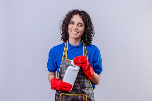 Grembiule d'uso della giovane donna e guanti di gomma che tengono bottiglia con i rifornimenti di pulizia che sorridono allegramente sopra la parete bianca