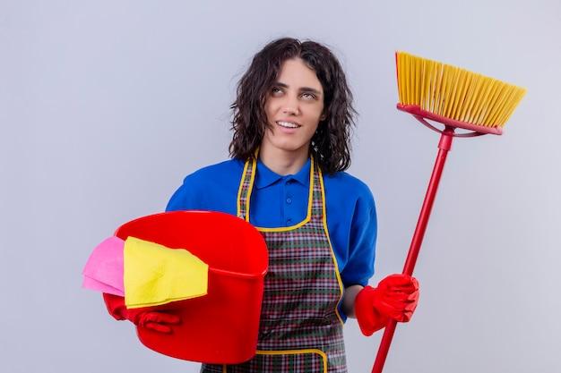 Grembiule d'uso della giovane donna e guanti di gomma che tengono secchio con gli strumenti e la zazzera di pulizia che cercano sorridenti e che pensano sopra la parete bianca