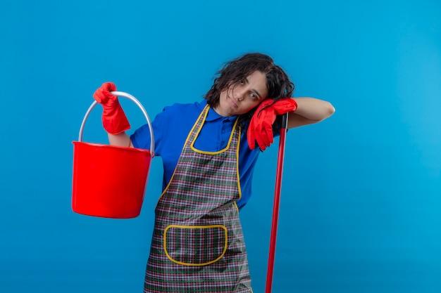 Grembiule d'uso della giovane donna e guanti di gomma che tengono secchio e zazzera che sembrano stanchi e sovraccarichi sopra la parete blu isolata