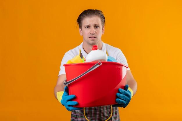 Grembiule da portare del giovane uomo di hansdome e guanti di gomma che tengono secchio con strumenti di pulizia