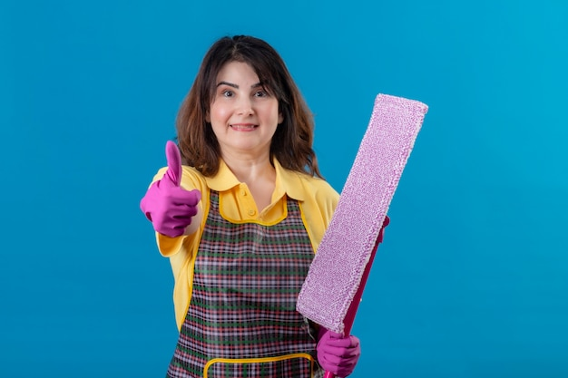 Grembiule da portare della donna di mezza età e guanti di gomma che tengono il mop che sorride con la faccia felice