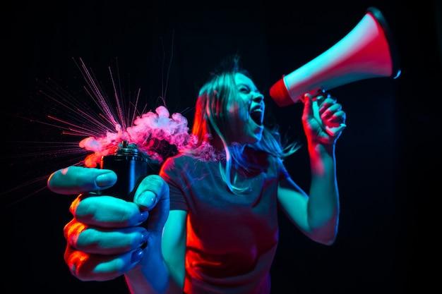 Gridando con il megafono. giovane donna con fumo e luce al neon su sfondo nero. alta tensione, grandangolo, vista fish-eye.