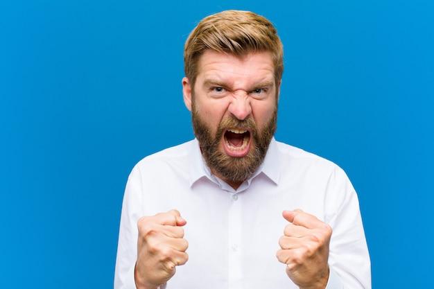 Gridare in modo aggressivo con sguardo irritato, frustrato, arrabbiato e pugni stretti, sentirsi furioso