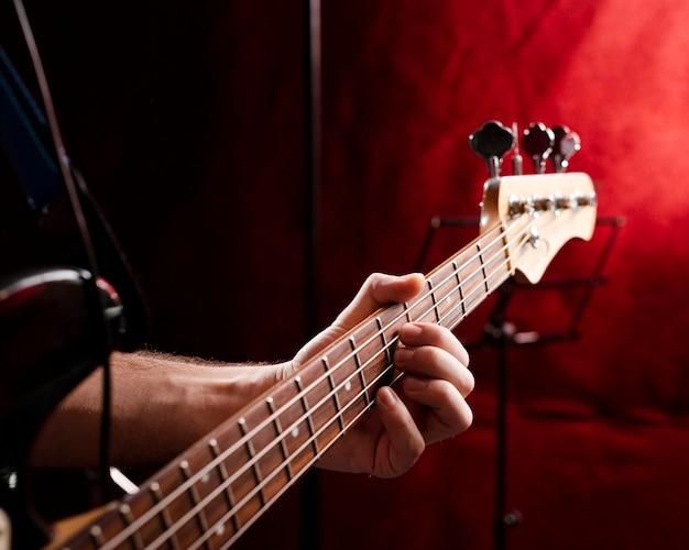 Grif del primo piano con le corde di una chitarra elettrica in studio