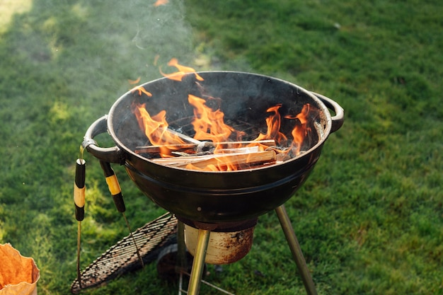 Griglia del barbecue con fuoco su erba al parco
