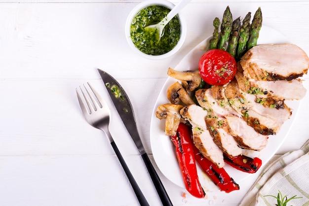 Griglia del petto di pollo con le verdure del bbq e la salsa di pesto in un piatto su legno