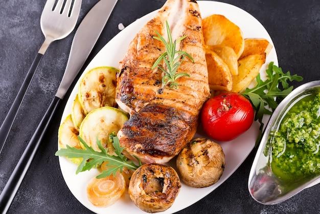 Griglia di petto di pollo con verdure alla griglia e salsa al pesto in un piatto