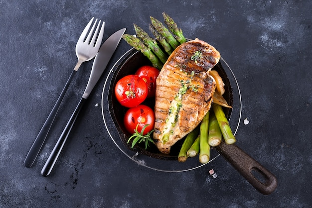 Griglia di petto di pollo con verdure grigliate e salsa al pesto in una padella di ferro su una pietra