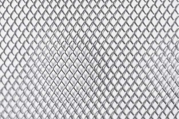 Griglia quadrata sul metallo bianco della parete
