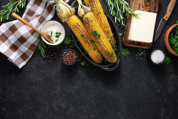 Grigliare il mais con burro, salsa cremosa, pepe, sale e rosmarino su fondo nero