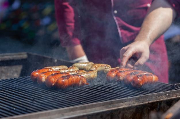 Grigliare le salsicce sulla griglia del barbecue. barbecue in giardino. festival del cibo di strada