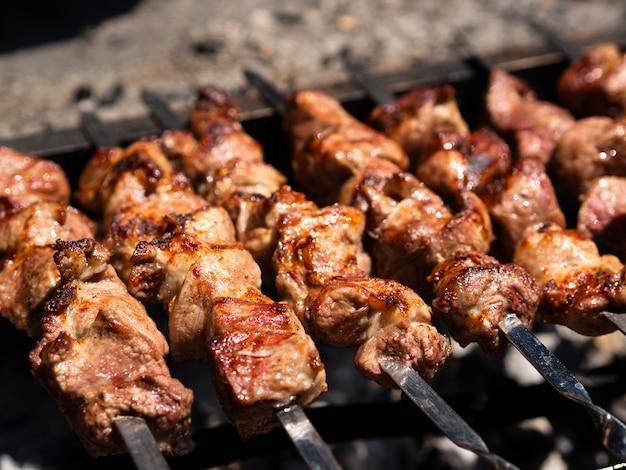 Grigliare shish kebab con crosta su spiedini