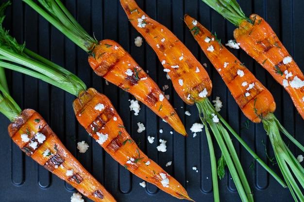 Grilleg carote con formaggio alle erbe e olio d'oliva. dieta sana e concetto di cibo vegetariano