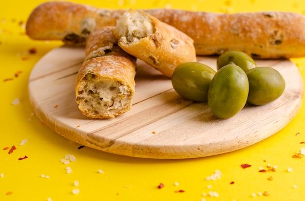 Grissini olivi rustici italiani su fondo giallo con lo spazio della copia