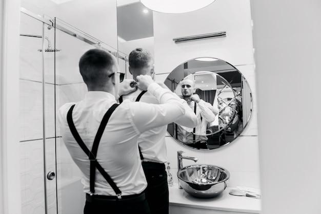 Groomsmen alla moda che aiutano sposo felice che si prepara al mattino per la cerimonia di nozze. uomo di lusso in tuta in camera. spazio per il testo. giorno del matrimonio.