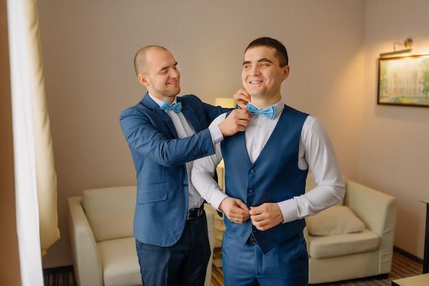 Groomsmen che aiutano sposo felice che si prepara al mattino per la cerimonia di nozze. preparazione del matrimonio dello sposo.