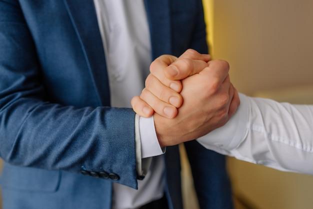 Groomsmen stringe la mano allo sposo e aiuta lo sposo felice a prepararsi al mattino per la cerimonia nuziale. preparazione del matrimonio dello sposo. avvicinamento