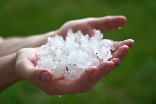 Grossi pezzi di grandine di ghiaccio nel palmo della tua mano. uomo che tiene in mano una manciata di grossi chicchi di grandine. conseguenze di anomalie naturali.