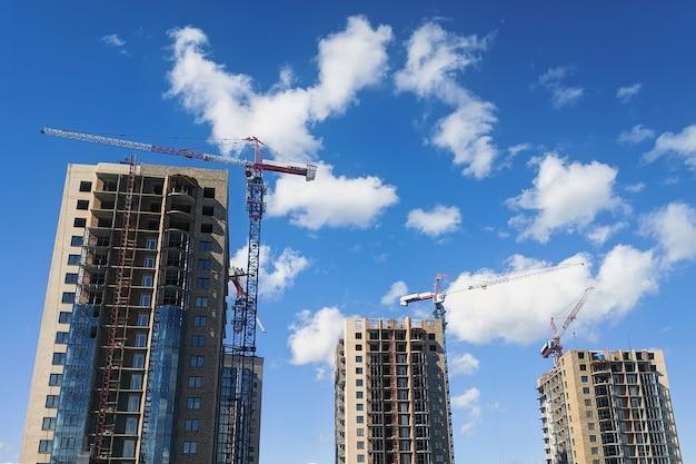 Gru a torre costruiscono case contro il cielo blu