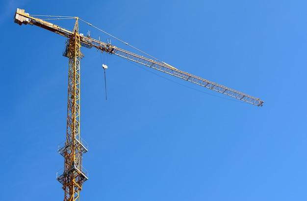 Gru a torre gialla mentre costruendo una casa contro un cielo blu