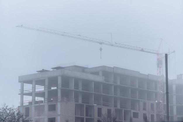 Gru da costruzione in tempo nebbioso sulla costruzione di edifici residenziali.