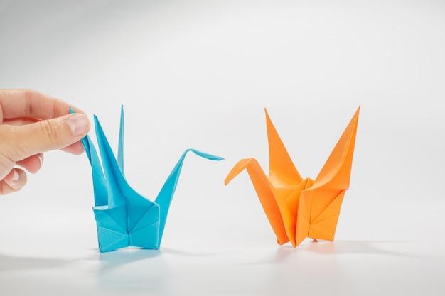 Gru di origami su superficie bianca
