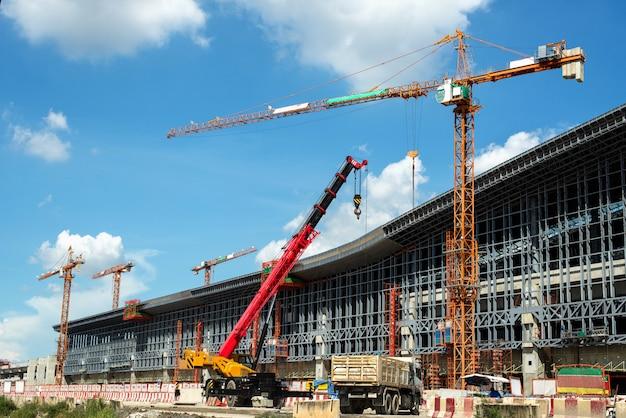Gru e lavori di costruzione di edifici e cielo blu