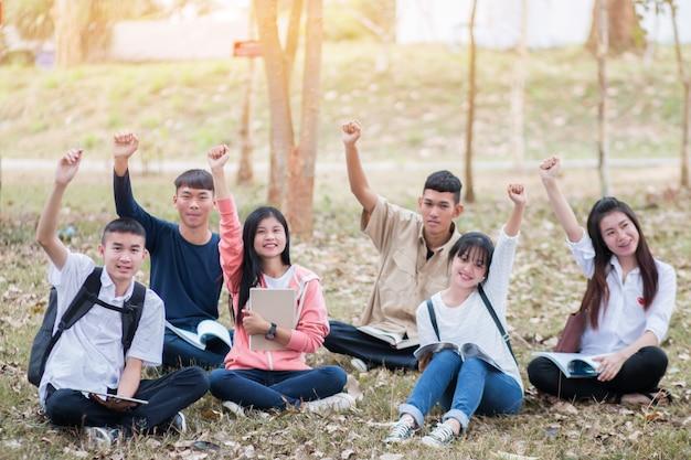 Gruppi di studenti asiatici fiduciosi che si siedono leggere il libro, utilizzare il computer tablet e hands up joy acc