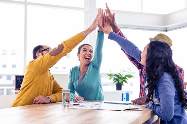 Gruppo allegro di affari che fa livello cinque mentre sedendosi nell'ufficio creativo