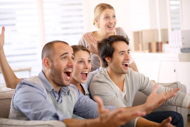 Gruppo allegro di amici che guardano partita di football americano in tv