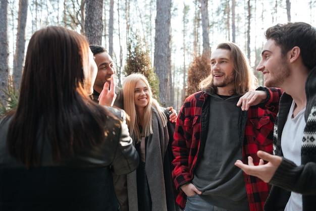 Gruppo allegro di amici che stanno all'aperto nella foresta