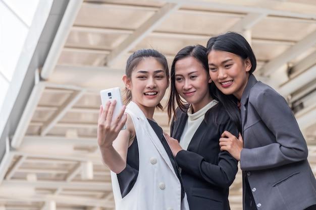 Gruppo alto chiuso di affari della giovane donna che mette all'aperto che prende un selfie
