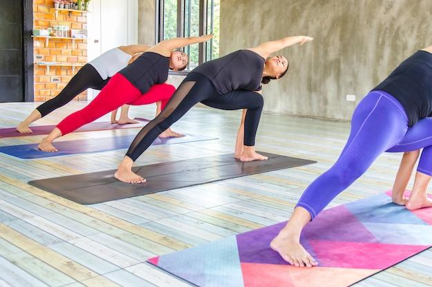 Gruppo asiatico femminile di forma fisica che fa posa di yoga di riscaldamento nella fila alla classe di yoga. messa a fuoco selettiva