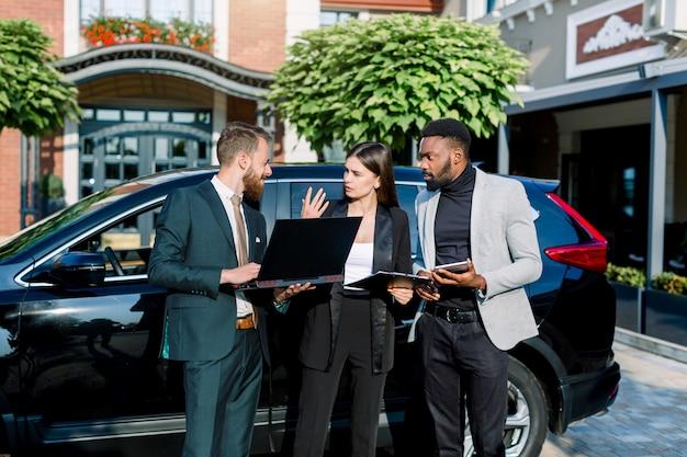 Gruppo aziendale multietnico, due uomini e donne che usano o esaminano tablet e laptop e discutono del lavoro e del progetto in piedi vicino all'automobile nera del crossover pronta per incontrarsi. concetto di affari.