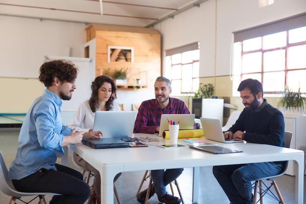 Gruppo creativo che lavora all'avvio, utilizzando laptop