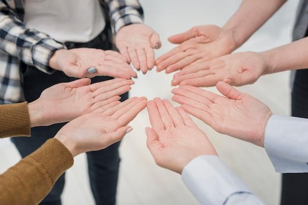 Gruppo del primo piano di donne con le mani in su