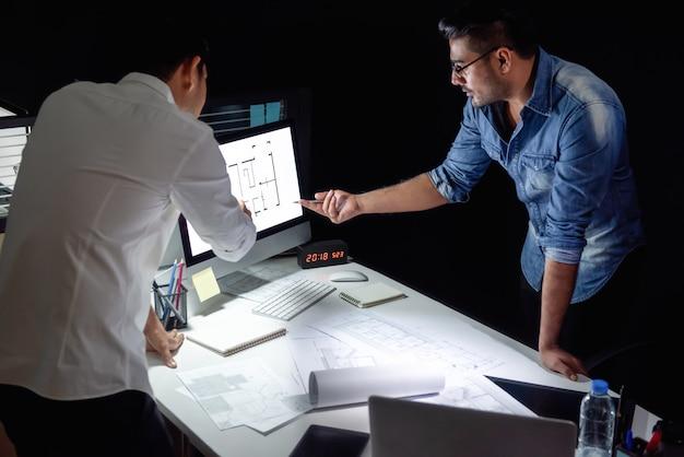 Gruppo dell'architetto che discute progetto alla notte