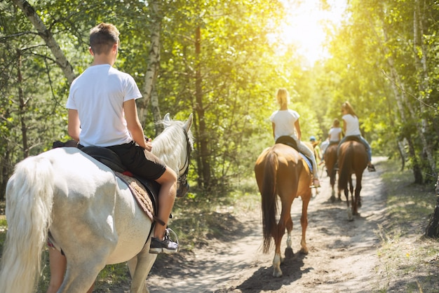 Gruppo di adolescenti a cavallo nel parco estivo
