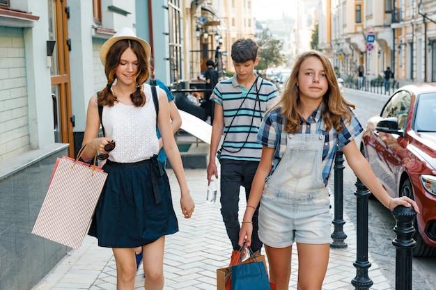 Gruppo di adolescenti con i sacchetti della spesa sulla via della città.