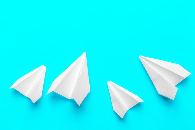 Gruppo di aerei di carta su sfondo blu.